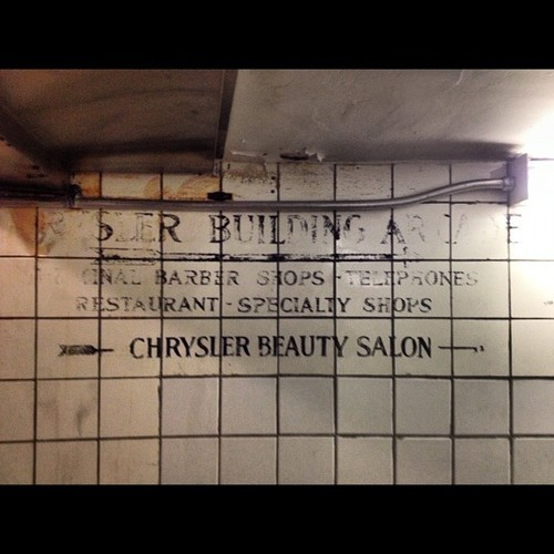 "Wonderful faded sign under the Chrysler Building for the Chrysler Building Arcade. It advertises a beauty salon, a barber shop, telephones, a restaurant and specialty shops. This would have been called a ""concourse"" had the Chrysler Building been constructed in the 1960s or 1970s. This survives where the arcade meets the Grand Central subway station. #nyc #architecture #transportation"