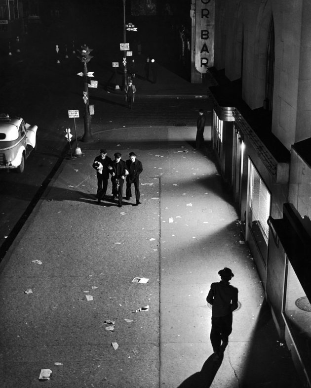 bygoneamericana:  A trio of sailors walk arm in arm down a dimly lit street near Times Square, searching vainly for fun in the curfew-quiet city. New York, 1945. By Herbert Gehr