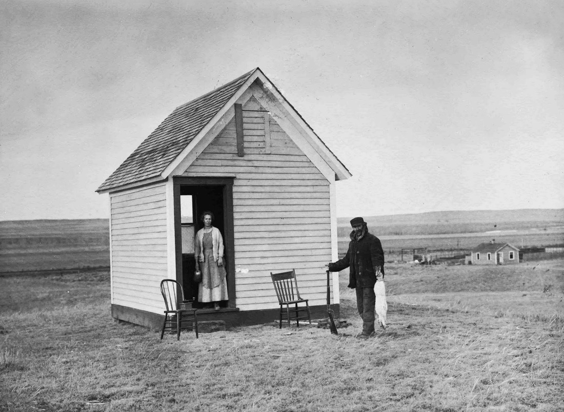 Olga Wold and her stepfather, Norman Wold, stand outside her homestead shack at Marsh, Montana. Photograph taken on December 28, 1912 by Evelyn J. Cameron.