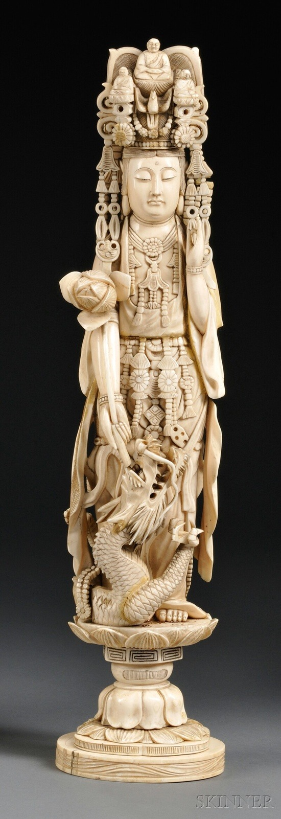 Kwan Yin, China, 19th century,  in adorned clothing and headdress, left hand in the mudra of appeasement position, right hand holding a lotus blossom, a swirling dragon at feet, standing on a lotus base.