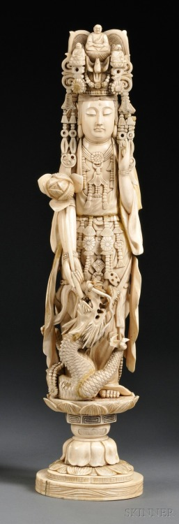 buddhabe:  Kwan Yin, China, 19th century,  in adorned clothing and headdress, left hand in the mudra of appeasement position, right hand holding a lotus blossom, a swirling dragon at feet, standing on a lotus base.