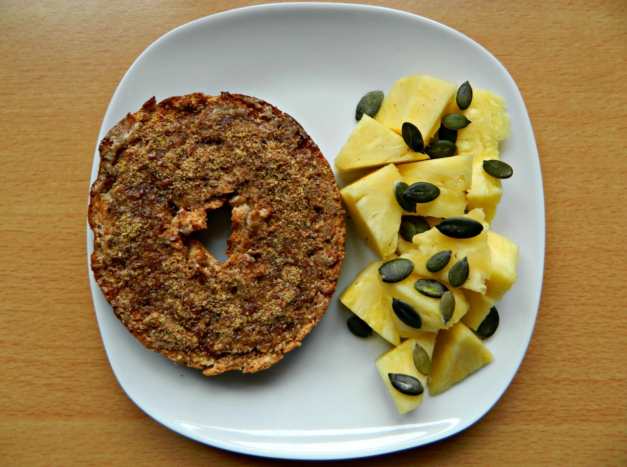 Half a wholewheat bagel with almond butter, ground flaxseed and agave, fresh pineapple and pumpkin seeds.