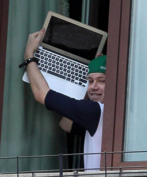 niall holding up his laptop at the hotel