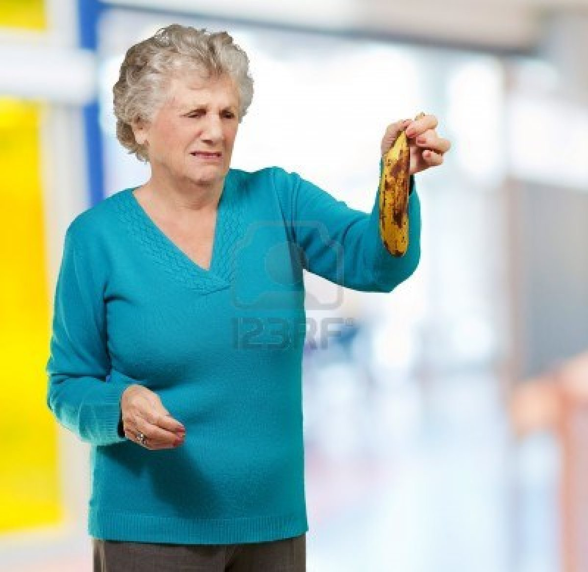 finegarten:  senior woman holding a rotten banana indoor