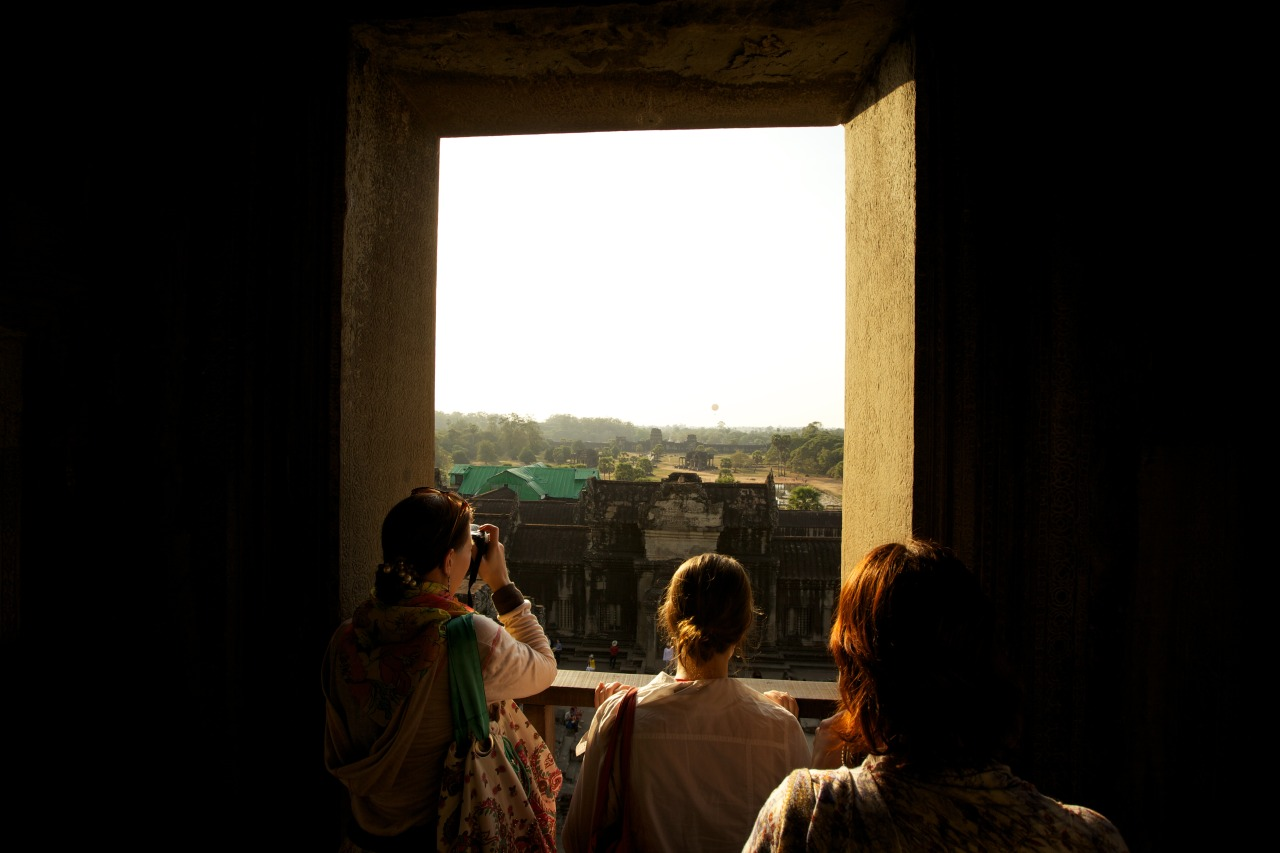 "Nearing sunset at Angkor Wat, January 2013.  We'd left Hong Kong that morning, taking a taxi 4:30am, with a driver that absolutely floored it to the airport. My dad said ""I've never had a cabbie go that fast"" and my mum said ""We were going fast?"" (she had fallen asleep). Transited in Ho Chi Minh City for a few hours, and then eventually made it to Siem Reap.  I found the heat that first day to be incredibly energy-sapping, probably due to a lack of sleep the night before (as my parents realised at about midnight they had forgotten to bring our e-visas for Cambodia). We wandered around this huge temple, and I saw how beautiful it was and I wondered how they managed to build such a huge structure without the help of modern machinery. I watched the beams of golden light stream through the windows, and saw how lovely everyone looked.  Once the sun had set, we had dinner and went back to the hotel. I pretty much passed out on the bed, I was so tired. It was a rather long but beautiful day."