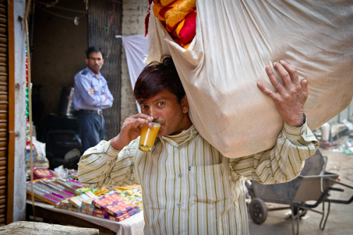 A man having morning orange juice on his way from market. Delhi, India.