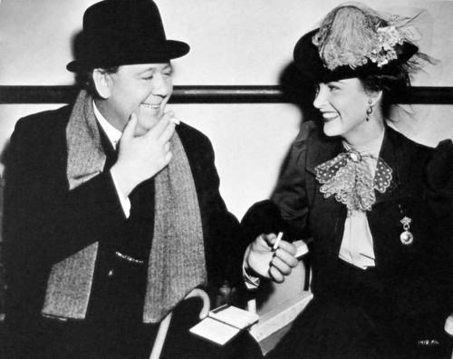 Charles Laughton and Ella Raines pause for cigarettes during filming of The Suspect.