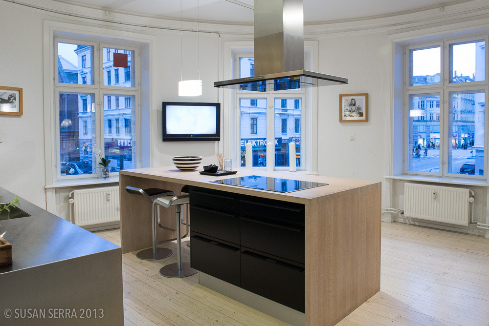 A showroom kitchen in Copenhagen, Invita, but it's a good argument for a kitchen design with large, low windows and it shows how nice a big connection to the outdoors feels. It means a little bit of a sacrifice of storage which should also be weighed. I can see a couple of comfortable upholstered chairs near the window to round out the kitchen as living space.