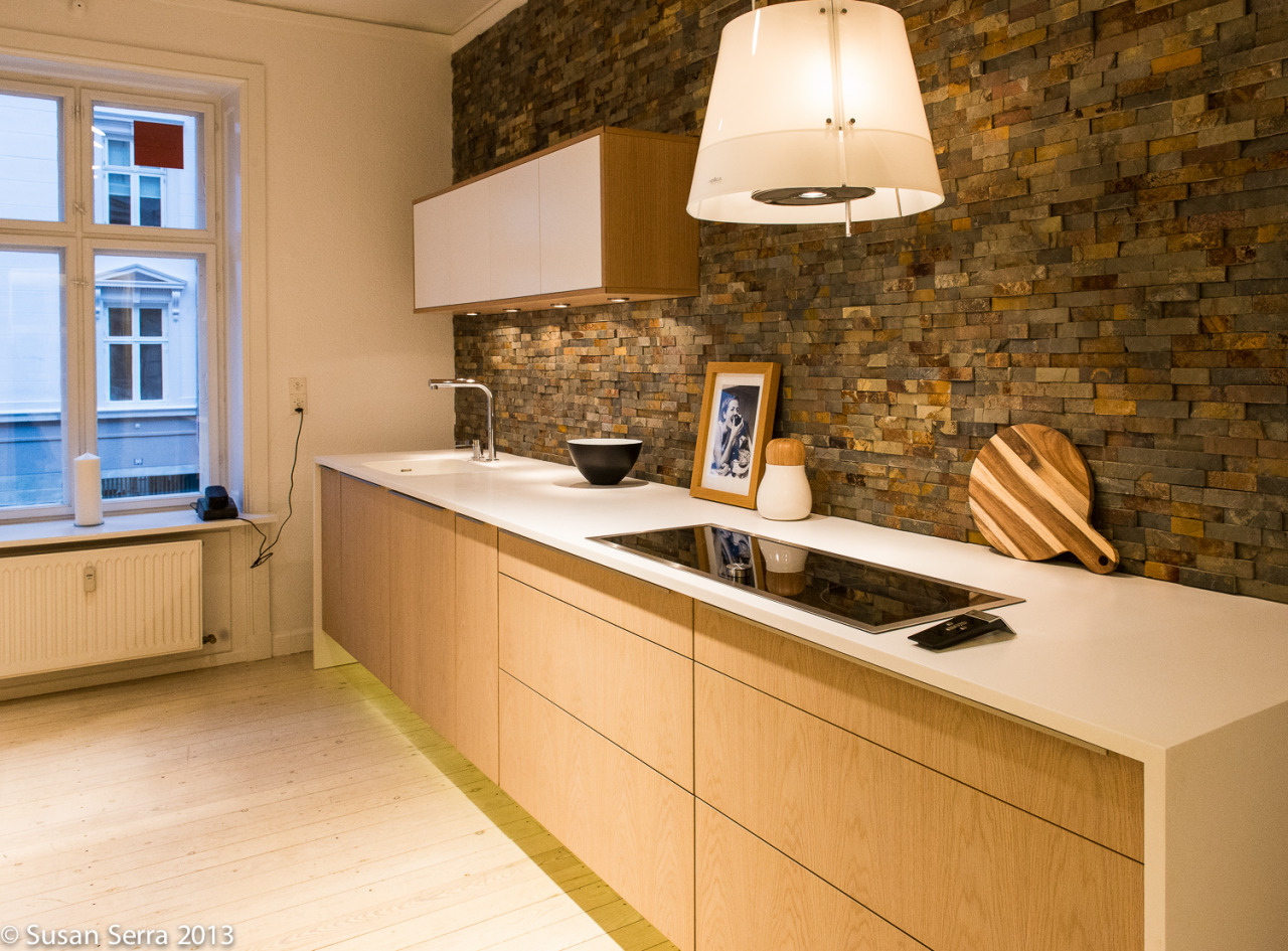 A beautiful kitchen display in the Invita showroom in Copenhagen. Natural flooring mixes with soft, modern design elements and strong texture in the backsplash adds excitement