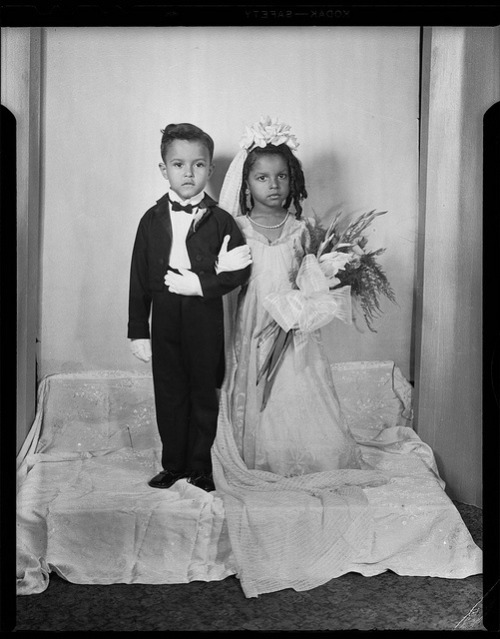 "LITTLE BRIDE & GROOM (YOUNG LOVE)Tom Thumb wedding portrait, with bride holding bouquet with gladiolus and large striped ribbon, posed in Charles ""Teenie"" Harris Studio c. 1945-1950"