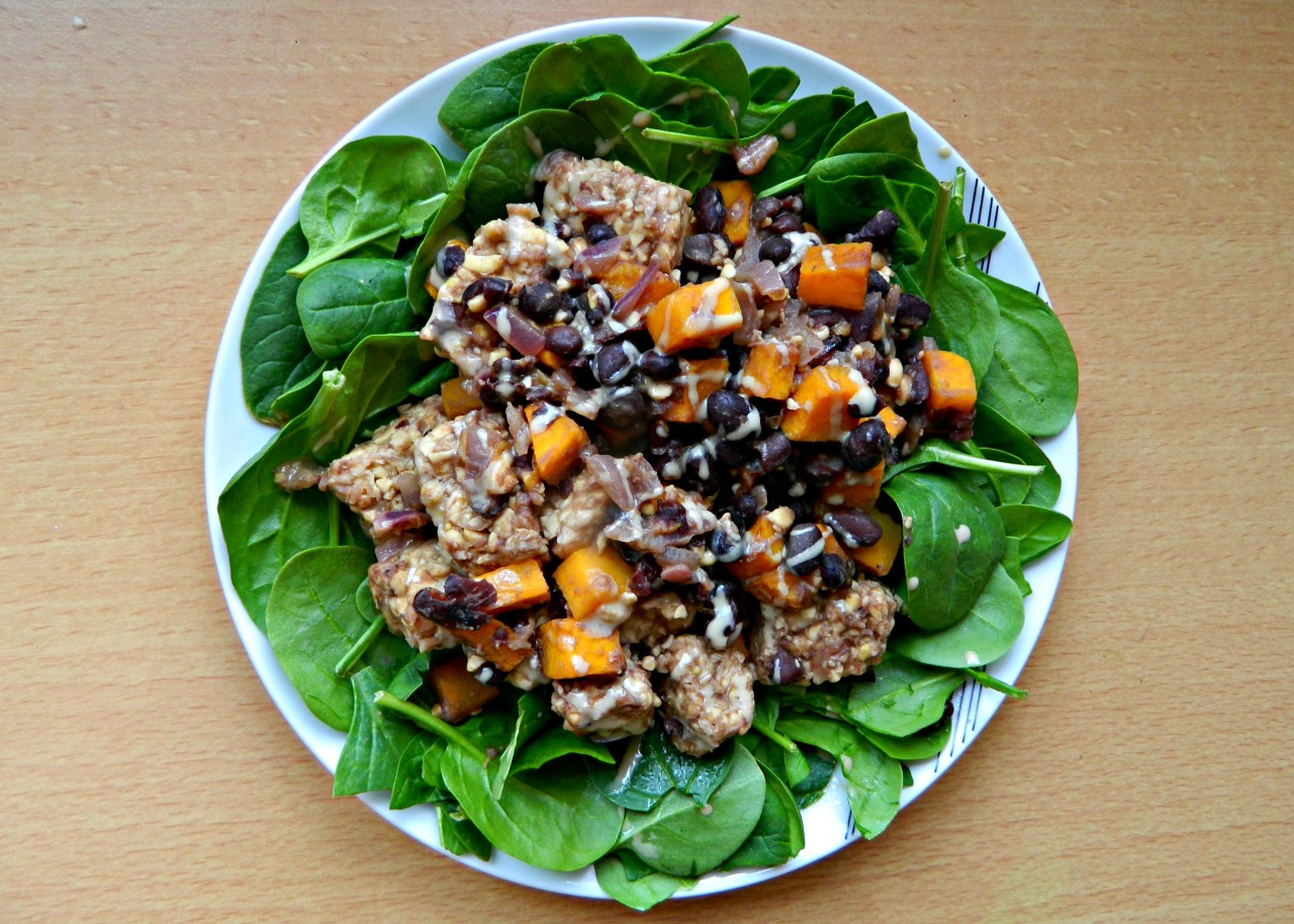 Tempeh, butternut squash and black bean warm salad with spinach and a drizzle of tahini. I cubed some b-squash and roasted it in the oven for 15 minutes with a little rapeseed oil, and whilst this was happening I sautéed some red onion, fresh ginger and garlic in a wok before adding the cubed tempeh. After that, I added some water to soften the tempeh and create a sauce, along with black pepper, soy sauce and pomegranate molasses. Once the b-squash was done, I threw it in the wok, gave everything a quick stir then served on a bed of spinach. Nom.  I'm pretty set on becoming 100% vegan again - but last time I was 100% vegan I know I didn't get enough protein, so I'm trying to make sure I have beans/pulses every day. Tempeh is a particularly awesome protein source if you're new to veganism - this 'salad' has 30g of protein, so it's definitely possible to get enough if you try. :)