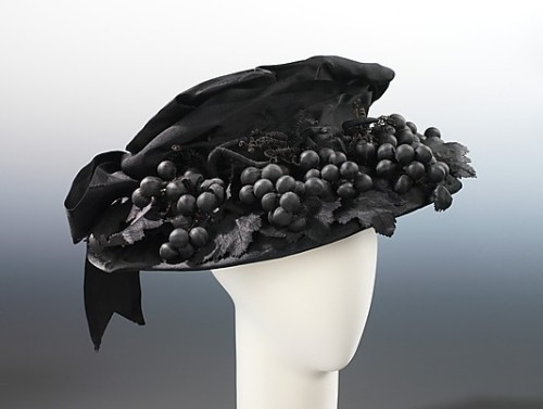 Mourning hat by Bruat, Inc, ca 1915 US, the Metropolitan Museum of Art  Black hats were popular for general wear in the 1910, particularly during the years of World War I, when sobriety and utility were the order of the day. Some hats, however, stand out specifically as mourning wear, suitable only to the bereaved, despite how chic the design might be. While this hat is fashionable in form and decoration, the unrelieved black clearly identifies its function. The choice of grape clusters - a normally colorful motif symbolizing fertility and abandon - produces an incongruous shock, thereby serving to strengthen the statement of mourning.