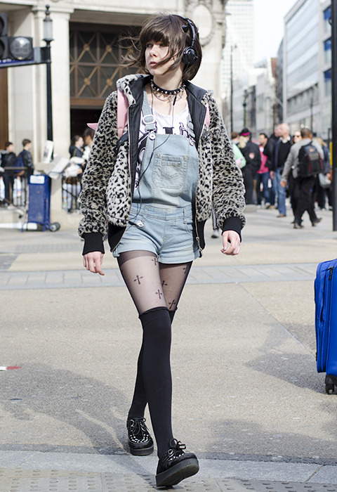 Untitled (acid washed short dungarees with creepers, over the knee socks worn over patterned tights, leopard print jacket, studded dog collar worn as necklace, headphones, pink rucksack and fringe)