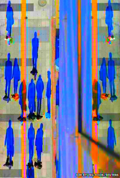 glitchnews (via slavin):  Pedestrians cast shadows on the pavement near the headquarters of the Bank of Japan in Tokyo.