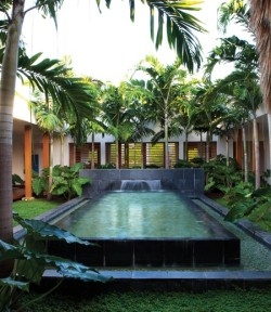 designed-for-life:  Modern Tropical Courtyard This retreat blurs the boundaries between outside and inside. A covered wooden walkway surrounds the interior courtyard, linking all the rooms that open onto it. Lush greenery and stately Royal palms frame the slate-lined reflecting pool and fountain.