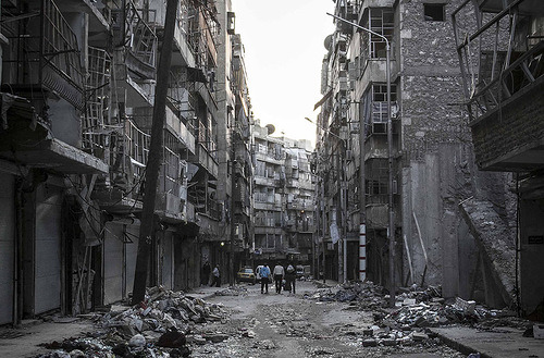 In this Saturday, Oct. 27, 2012 photo, Syrian residents walk on a street among the debris of buildings shattered by heavy shelling in Tarik Al-Bab neighborhood, southeast of Aleppo City.  (AP Photo/Narciso Contreras).