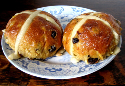 Hot Cross Buns from St John Bread & Wine (Spitalfields) via Consider the Hot Cross Bun   The OED's first reference to [Hot Cross Buns] dates to 1733 and the familiar nursery rhyme, but the buns are far older than that. The Ancient Greeks baked small loaves to mark the spring, and even the Egyptians offered breads marked with the image of ox horns to their goddess of the moon. When archaeologists excavated the Roman city of Herculaneum – buried by the same explosion that preserved Pompei – they found two small, carbonised loaves among the ruins, each marked with a cross. The pagan Saxons baked breads slashed with crosses to honour Eostre, their goddess of spring and fertility and the source of our word Easter. The four sections symbolised the four quarters of the moon, or the seasons, or something else.   The truth is that the cross is such a common, ancient sign it can represent almost anything. And since one can yoke so many meanings to the symbol, breads decorated with it have developed an exceptional number of superstitions and legends. It was popularly believed that a bun baked on Good Friday would never go mouldy, that if it was hung in the kitchen it would improve a cook's baking and prevent fires from breaking out, and that if you stashed a bun in a heap of corn it would keep the rats and weevils away. One Lincolnshire family has apparently kept a hot cross bun in a box since 1821.   Sailors, always a superstitious lot, took buns to sea hoping they might ward off shipwreck. There's a pub in the East End called The Widow's Son, named after a woman who lived on the site in the 1820s and who baked some hot cross buns for her son who was due home from sea that day. He never arrived, but she continued to bake a bun for him every year and hang it in the kitchen. Every Good Friday, a dozen or so members of the Royal Navy present the pub with a large hot cross bun in memory of the lost sailor, and the pub tells me it lays on free hot cross buns and other food for anyone who drops in for a drink.    How to make perfect hot cross buns via The Guardian