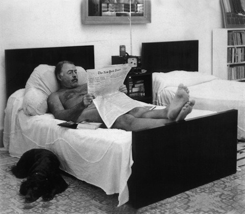 Ernest Hemingway reading The New York Times in bed, naked – can't cover as much with an iPad… By his side, surprisingly, a dog. Photograph by George Leavens.