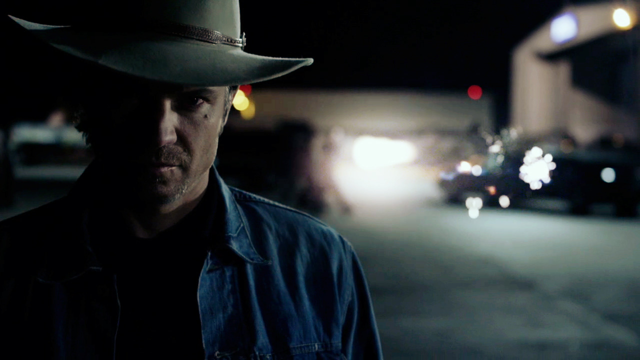 """4x13 – Ghosts  """"Tell him the game's the game, but you don't go after a man's family.""""  The scene with Raylan and Boyd in the truck. Thirteen episodes of the season, fifty-two episodes all told, and that's what I want to know, who wrote the scene with Raylan and Boyd in the truck? Was it one of those full-grown, first-draft lightning strikes of brilliance that stayed untouched throughout? Was it a never-ending revision, a head-acher or hair-puller, everybody on staff and on set tweaking word-by-word down to the wire? Probably, someplace in between but, as much as I'd like to believe there's a brain that has these voices so clear in their head, I'm guessing it's closer to the latter. The whole conversation, the blows land with millimeter-precisio"""
