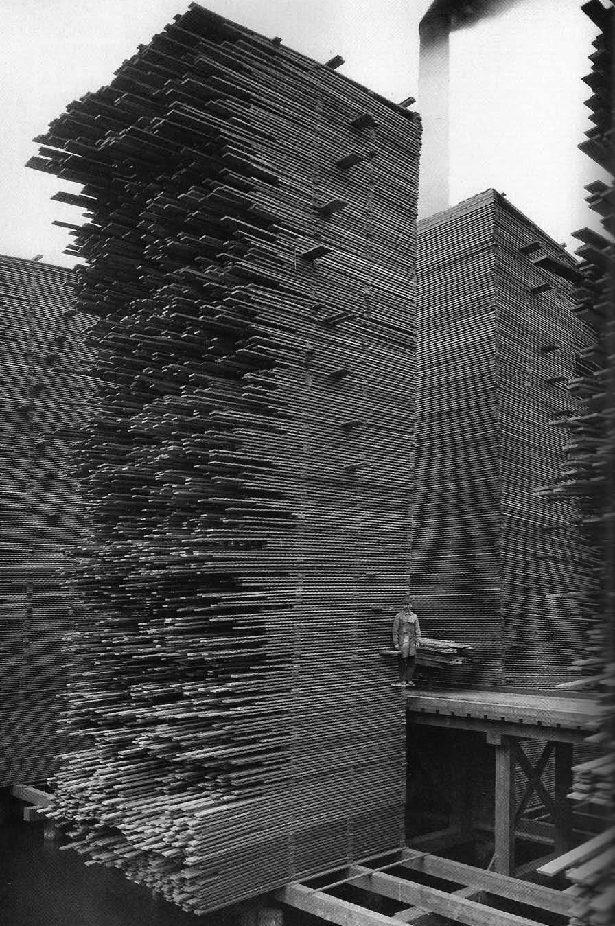 """© Webster & Stevens, ca. 1919, Stacks of lumber drying, Seattle  The Cedar Lumber Manufacturing Company's mill, located just west of the Ballard Bridge, was the largest in Ballard. At the mill, logs were cut into lumber which was then dried for at least nine months before being sold. The stacks of drying lumber were over 50 feet high. In 1958, these stacks caught fire and burned. Ballard residents remembered the huge blaze for many years. (+)  This reminds me of my grandfather's """"lumberyard"""" that my brother and me used as adventure playground when we were kids. My grandfather used to be """"Wagnermeister"""", now an extincted job: he was more or less a carpenter who was specialized in the construction of horse carriages and cartwheels (German: """"Wagen"""" = cart, carriage)."""