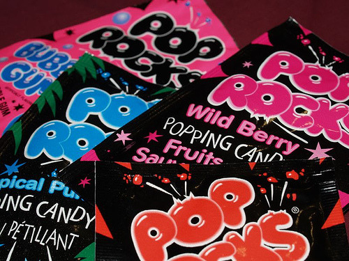 certaintendencies:  Why Pop Rocks Pop  Hard candy (like a lollypop or a Jolly Rancher) is made from sugar, corn syrup, water and flavoring. You heat the ingredients together and boil the mixture to drive off all of the water. Then you let the temperature rise. What you are left with is a pure sugar syrup at about 300 degrees F (150 degrees C). When it cools, you have hard candy. To make Pop Rocks, the hot sugar mixture is allowed to mix with carbon dioxide gas at about 600 pounds per square inch (psi). The carbon dioxide gas forms tiny, 600-psi bubbles in the candy. Once it cools, you release the pressure and the candy shatters, but the pieces still contain the high-pressure bubbles (look at a piece with a magnifying glass to see the bubbles). When you put the candy in your mouth, it melts (just like hard candy) and releases the bubbles with a loud POP! What you are hearing and feeling is the 600-psi carbon dioxide gas being released from each bubble. (full article here)