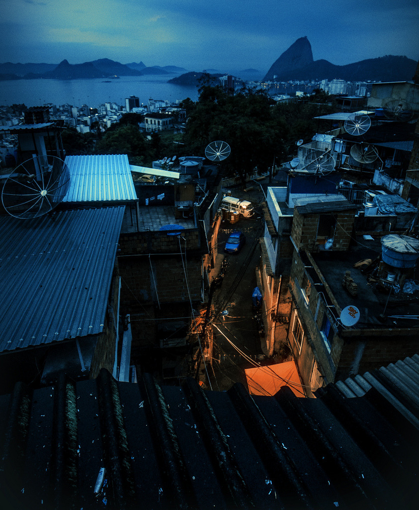 "Brazil (by [brett walker]) ""A serene well-to-do town, beautifully nestled and safe among those majestic mountains, winding down for the night, coolly indifferent to the makeshift pockets at the heart of it where the activity is just heating up. Even the satellite dishes seem to be on guard, acting as sentries to the goings-on that will be taking place below them through the night. The complimentary colours accentuate the opposing facets of how differently life is lived within this tale of two cities."""