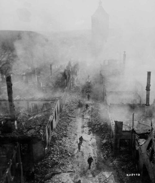 ww2inpictures:  American soldiers walk through the smokey ruins of a desolated street. Waldenburg, Germany.