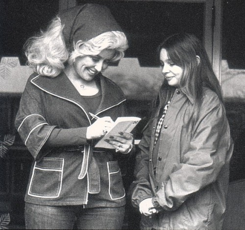 Dolly Parton signing an autograph for a young fan. Circa 70's.