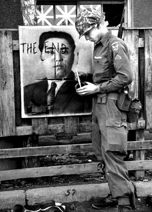1bohemian:  A paratrooper paints the end to the Red Premier. North Korea, 1950.  Howard Sochure