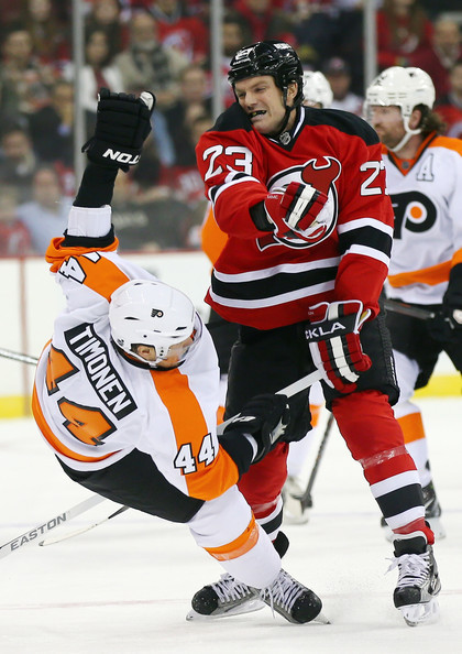 David Clarkson #23 of the New Jersey Devils checks Kimmo Timonen #44 of the Philadelphia Flyers during the season opener at the Prudential Center on January 22, 2013 in Newark, New Jersey.