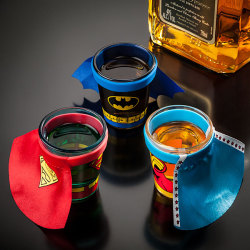 bennyneedsthis:  What Benny Needs: DC Comics Caped Shot Glass Why Benny Needs This: Lazarus had his pit, He-Man had his power sword, and Benny has his whiskey. Nothing gives you the courage of a lion or the strength of a locomotive like a nice shot of Jameson. It also makes you seem better looking to people you think are better looking than you but are really not and vice versa.Capes just make everything more heroic. It's a god given, scientific fact. The reason you don't see people wearing capes nowadays is because no one is super. Everybody sucks. So why not drink yourself into an alternate universe with an officially licensed piece of DC property. When you take the capes off, the shot glasses go back to their secret identities as… shot glasses; on your shelf. Put the cape back on and it's like you're performing oral sex on a caped crusader. Just remember that there are no such things as special powers and after taking several shots of your favorite elixer to the head, you'll turn into a sobbing, sloppy mess and your superhero name will be Douchebag. Thanks go out to Elizabeth F. for the submission. I can't keep up with everything Benny needs so every little bit helps. Excelsior!