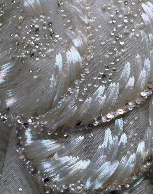 "fashioninhistory:  'Venus' Evening Dress (Detail) Christian Dior Autumn/Winter 1949 This extraordinary ball gown by Christian Dior, of foggy gray silk tulle, arrayed with an overlay of scallop-shaped petals, is called ""Venus."" The bodice and shell forms of its skirt are embellished with nacreous paillettes and sequins, iridescent seed beads, aurora-borealis crystals, and pearls. The glittering overskirt and train adumbrate both the seashell motif and the crescent wave patterns of Botticelli's Venus."