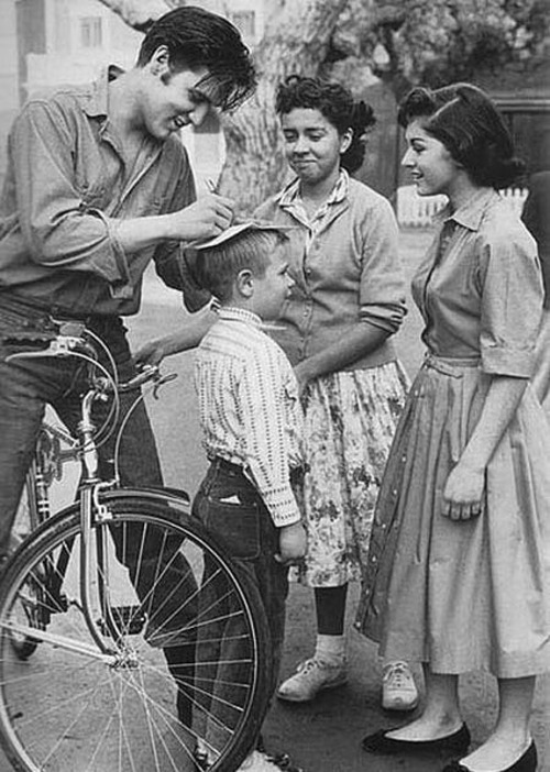 Biking Elvis Presley Stops to Sign Autographs on A Little Boy's Head A little less conversation, a little more autographs, please!