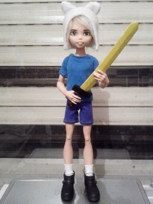 "oak23:  Here is my Finn the Human doll from Adventure Time. He is a Gloom Beach Draculaura head on a Scaris Deuce body with a shortening mod on his legs to make him look more youthful in comparison to my other dolls. His head was blushed to match his body and he has fur glued onto his scalp. His clothes were all made by me except his shoes which are an Action Figure's boots trimmed down to size and his sword is from the Jazwares Adventure Time 10"" Finn."