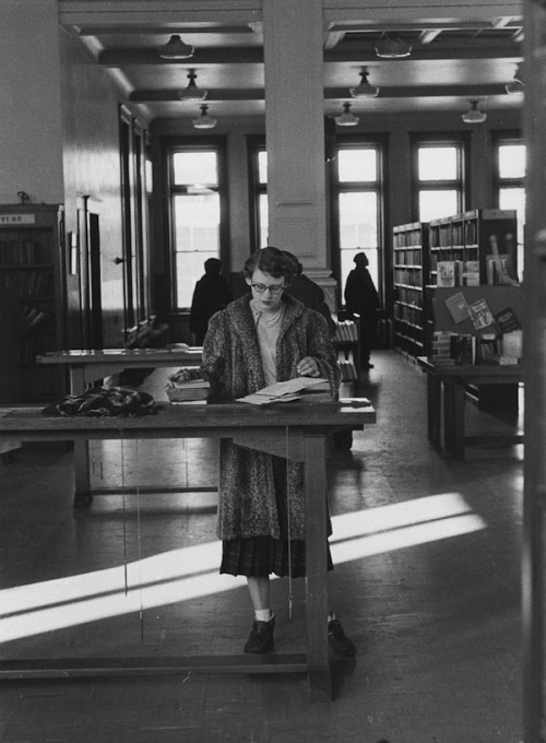 theniftyfifties:  A girl with glasses in the library, 1955. Photo by Michel Lambeth.