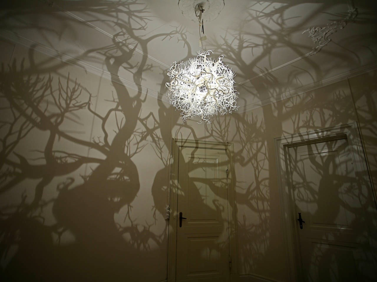 itscolossal:  This chandelier from Hilden & Diaz projects the shadow of a forest into your room!