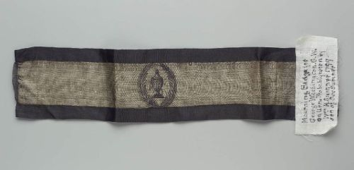 "Mourning band for George Washington, 1799 Boston, the Museum of Fine Arts Boston  Mourning band for George Washington (d. 12/14/1799), white ribbon with painted design of urn inscribed ""GW"" in wreath, edged with black silk and covered with black silk crepe Inscription Written in ink of fabric label sewn to object: ""Mourning Badge for George Washington. G.W. on urn. Probably worn by Wm. H. Sumner [1780-1861] 1799, son of Gov. [Increase] Sumner [1746-6/7/1799]"""