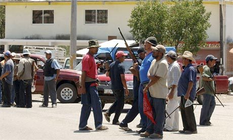 Armed men stand at the entrance to the town of Tierra Colorada, Mexico, where vigilantes have arrested local police and officials accused of gang links. Photograph: Alejandrino Gonzalez/AP