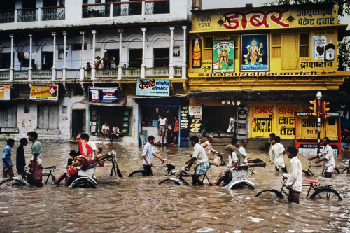 stevemccurrystudios:  Cycling through the flooded streets of Varanasi, Uttar Pradesh, Northern India during the monsoon.