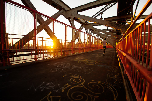 "The Williamsburg Bridge at sunset. New York City.  When the sun sets in the winter, its light pours over the city like the glow from a distant bonfire with scattered light illuminating the grey, steel edges like embers strewn about in the wind.  —-  I took this image yesterday with the Sony a99 while walking over the Williamsburg Bridge. The Williamsburg Bridge is a favorite of mine in lower Manhattan. It tends to be overshadowed by the Brooklyn Bridge and Manhattan Bridge when it comes to popularity. This is probably because its pedestrian walkway is completely enclosed by a metal gate and because it isn't in super close proximity to the other two bridges (although one could argue that the pedestrian entrances to all three bridges are in walking distance to each other).   However, it definitely lives up to its National Historic Civil Engineering Landmark status. Its architecture is incredible and the views of the New York City skyline and Brooklyn that can be glimpsed from either walkway are stunning.     —-  View this photo larger and on black on my Google Plus page —-  Buy ""Williamsburg Bridge Sunset - New York City"" Posters and Prints here, email me, or ask for help."