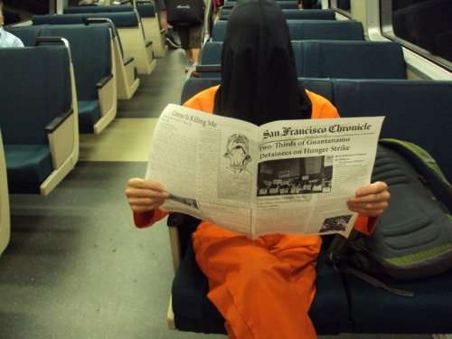 "maymay:   Escaped Guantanamo Prisoners Spotted on BART As the massive hunger strike among prisoners at Guantanamo enters its third month, Bay Area activists took to the rails to raise awareness of this escalating human rights violation. Inspired by an action organized by the London Guantanamo Campaign, anti-torture activists boarded BART trains on Saturday wearing the iconic orange jumpsuits and black hoods associated with detainees at Guantanamo. Somewhat ironically, the hooded prisoners read a newspaper filled with news about the prisoners' hunger strike, which after two months has finally succeeded in doing what none of us have been able to do for the last 11 years - awaken public awareness and discussion of the ethical and legal problems of holding people indefinitely with no charges.  86 of the 166 prisoners held by the US at Guantanamo have been cleared for release, but have little hope of being free. The vast majority of the others are ""considered dangerous"" by the Pentagon and CIA but can never be tried for any crime, either because there is no evidence against them or because what there is was obtained through torture.  Transit riders were engaged by the theater, actively requesting copies of our flier. Hopefully that translates into action and people will pressure Obama not only to follow through on his promise to ""close Guantanamo"" but to release the detainees or prove they are guilty of a crime. http://www.actagainsttorture.org/  Brilliant. Theatrical protests are the best protests. (↬ Indybay.org)"