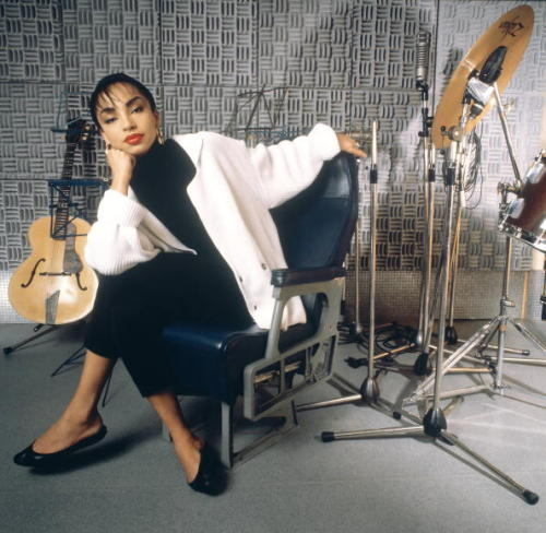 vintageblackglamour:  Sade, born Helen Folasade Adu in Ibadan, Nigeria, turns 54 today! In this 1985 photo (Gered Mankowitz/Redferns) she is at a recording studio on Willesden High Road in London.  Classic woman!