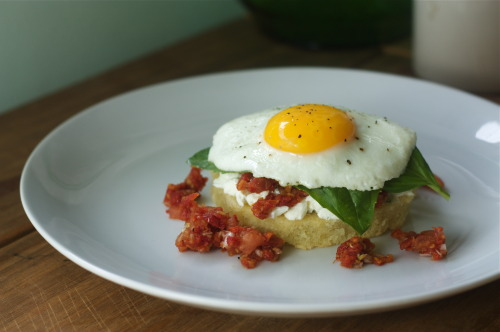 "Open-Faced Egg Sandwich inspired by the ""Tomato Burger"" from Blue Hill (via NYT's Recipe)As some of you may know, my day/night/weekend job is as an event planner for a catering company here in Brooklyn.  Part of what I do is discussing menu ideas with couples/clients and discussing how to bring their backgrounds, family recipes and inspiration from their favorite restaurants into their menu.  Recently a couple had mentioned how much they love Blue Hill Farm's ""tomato burger,"" so I had our chefs do a take on it for their tasting.  I got to sample it myself and was so obsessed with the balance of sweetness from the ""bun,"" the savory tomato and the creamy goat cheese, I made a mental note to try it at home.  As someone who loves savory and sweet breakfast foods together (""don't judge me!"" I exclaimed as I dumped syrup all over my eggs and potatoes the other morning), I thought this would be perfect with a delicious sunny side up egg on top.  Serves 4 For the ""bread""1/3 cup + 1 Tbsp Almond Flour1/3 cup + 1 Tbsp All-Purpose Flour3/4 cup Powdered Sugar2/3 cup Extra Virgin Olive Oil (honestly, I would recommend using less than their recommendation - it turned out a lot heavier and greasier than I would have liked.  Might reduce as much as half next time.) 1/2 tsp Salt4 large Egg Whites, lightly beaten Preheat oven to 325.  Coat a 9x9 baking pan with cooking spray.  In a bowl, whisk together dry ingredients.  Pour in egg whites and whisk with dry ingredients until combined.  Continue to whisk and slowly add olive oil in a stream.  Pour into baking pan and bake on middle rack for 20-25 minutes or until golden yellow.  Remove from oven and allow to cool.Tomato Filling: 2 pounds ripe Tomatoes1 cup Sundried Tomatoes in oil, drained and finely chopped1/4 Tbsp Shallots, finely chopped1/2 Balsamic VinegarCut a shallow x in the bottom of the tomatoes.  Blanch in boiling water for 30 seconds.  Remove from heat and run under cold water.  Skins should easily slip off.  Remove seeds and chop into a small dice.  In a bowl, toss together diced tomato, sundried tomato, shallots, balsamic vinegar and season with salt and pepper.  Goat Cheese Filling:2/3 Goat Cheese, room temperature6 Tbsp Mascarpone Cheese, room temperature 2 Tbsp chopped Chivespinch of saltStir together all of the ingredients and set aside.Egg:4 Eggs2 TbspSalt & Pepper to tasteFresh basilMelt butter in a pan.  Crack eggs into pan and cook on low/medium heat until whites begin to firm up.  Cover with lid until whites are about done.  Season with salt and pepper.To assemble:Cut a four rounds out of the ""bread.""  Layer each with some of the goat cheese, a generous amount of the tomato filling, fresh basil and top with an egg.  Serve hot.  Hey! You should like The Bored Vegetarian on fb!"
