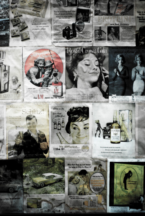 Shop window in DUMBO, Brooklyn, New York, boarded up with 50s & 60 magazine adverts. by Alex Bateman