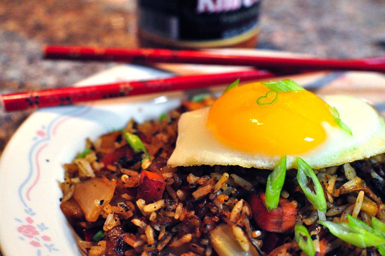 Kimchi Fried Rice [[MORE]] — Being a college student often means learning how to eat on a tight budget. The easy solution is making fried rice dishes. One of my favorites is Kimchi Fried Rice.  I like to load my fried rice with plenty of vegetables, chicken, and of course, Kimchi!   Best of all, the dish is topped with a fried egg. The yolk runs into the rice, making each spicy, sour, and salty bite even more rich and flavorful.   Kimchi Fried Rice 2 tbsp oil 1/2 onion, diced 1 red bell pepper, diced 1 carrot, peeled and diced 1 cloves garlic, minced 1/2 lb chicken, cubed 1 cup kimchi, chopped 1/2 cup spinach, chopped 2 tsp soy sauce 2 cups cooked rice (preferably day old)  Salt, to taste 2 eggs, cooked sunny side up 1 scallion, thinly sliced — In a nonstick skillet over medium high heat, saute the onion, bell pepper, carrot, garlic, and chicken with the oil for about 5 minutes, or until the vegetables are tender and the chicken is browned. Add the kimchi and spinach and saute for another minute, until the spinach begins to wilt. Add the soy sauce and rice. Cook for another 5 minutes, or until the rice begins to brown. Season with salt to taste. Pour into serving dishes and top with sunny side up eggs and sliced scallions. Makes 2 servings.