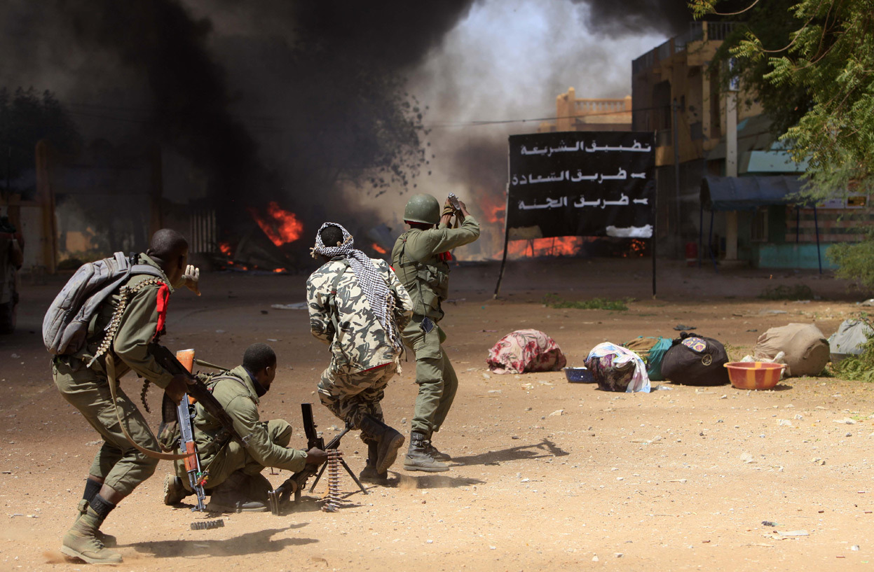 From Mali Conflict Enters New Phase, one of 37 photos. Malian soldiers fight while clashes erupted in the city of Gao on February 21, 2013 and an apparent car bomb struck near a camp housing French troops as Malian and foreign forces struggled to secure Mali's volatile north against Islamist rebels. (Frederic Lafargue/AFP/Getty Images)