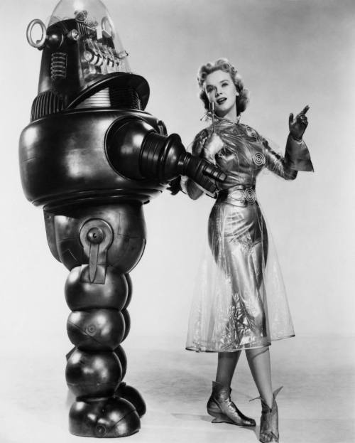 althistories:  Robby the Robot poses with co-star Anne Francis in this shot for 1956's Forbidden Planet, a brilliant and visually stunning retelling of Shakespeare's The Tempest.
