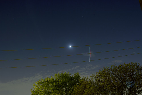 hanging on a line. (waxing crescent moon and light trails of a passing airplane)