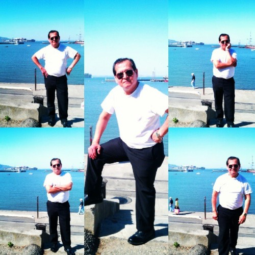 Photoshoot de mi Papá en aquatic park. Tiny Alcatraz behind, covered in pink flowers.