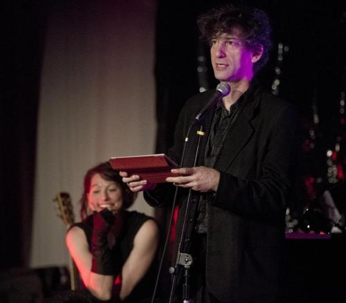 "Gala on calendar for Gaiman and Palmer ""American Gods"" and ""The Sandman"" writer Neil Gaiman and his wife, Lexington-bred Dresden Dolls frontwoman Amanda Palmer, kept their promise over the weekend by spending the last night of the Mayan calendar in Dorchester with locals who are turning a neighborhood firehouse into a space for visual and performing arts. Gaiman and Palmer performed at the Friday night Gala Party for Torrent Engine 18, which is being turned into an art space by Katherine Bergeron — a.k.a. performer Katrina Galore — and E. Stephen Frederick, of the Empire S.N.A.F.U. Restoration Project. Guests donated $125 to get a ticket to the party, which also featured a burlesque performance and some stage time with Bergeron. The appearance by Gaiman was especially timely for fans who read on his website last week that his next book-signing tour will be his last. Gaiman explained in a blog post that book tours are exhausting for writers, and that ""I love meeting people, but the sixth hour of signing, for people who have been standing in a line for seven hours, is no fun for anybody. (The last proper US signing I did, it lasted over 7 hours and I signed for over 1,000 people. I'd suspect a lot of the signings on this tour will be like that, or bigger.)"" Gaiman, whose forthcoming novel is ""The Ocean at the End of the Lane,"" told the Globe before Friday's party that he won't disappear on fans, and that he will absolutely continue to tour with his books — he just won't sit for hours and autograph each one. He joked that when he does his final signing tour for ""Ocean"" next year, he'll wind up ""plunging [his hand] into bags of frozen peas."" ""But I love the book and I'm really proud of it,"" he said. ""And if I'm going to go out, I'm going to go out with a bang."" http://www.bostonglobe.com/lifestyle/names/2012/12/24/neil-gaiman-book-tours-and-frozen-peas/JaLyK6IWolQMRjztTubncI/story.html"